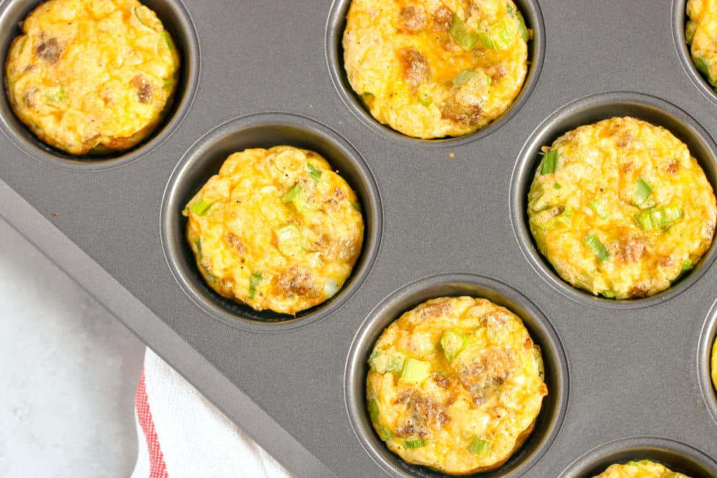 a horizontal image with a corner shot of the sausage egg muffins in the tin
