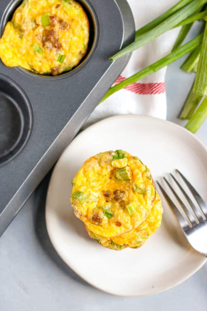 two sausage egg muffins stacked on top of a plate next to the muffin tin with green onions