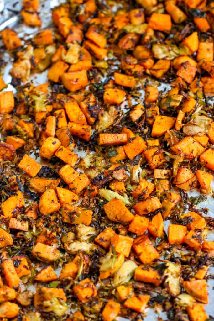 a close up of roasted shaved brussels sprouts and sweet potatoes on aluminum foil