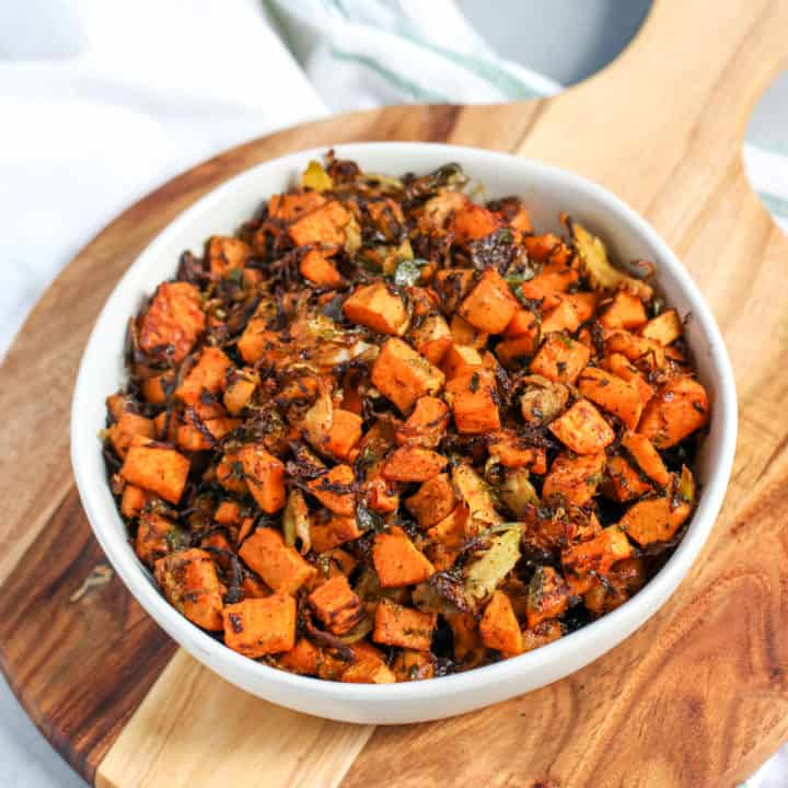 a bowl of roasted shaved brussels sprouts and sweet potatoes sitting on top of a wooden platter
