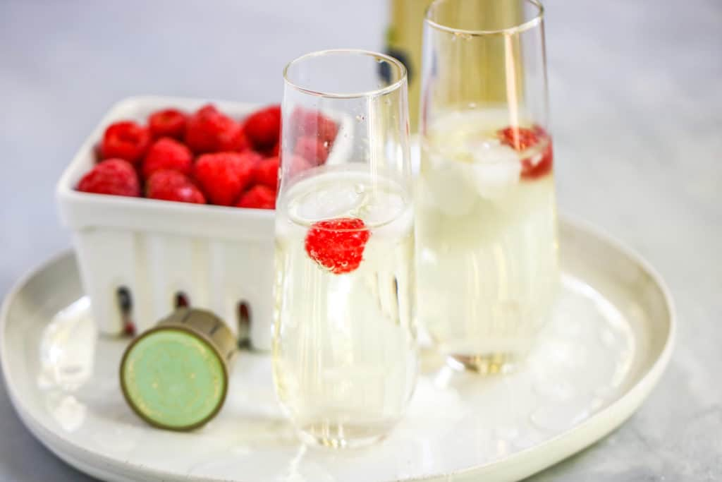 two stemless champagne flutes with the st. germain cocktail and a berry basket of raspberries