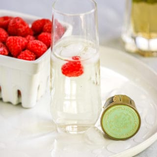 a stemless champagne flute with the st. germain cocktail and a raspberry