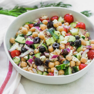 a bowl of Mediterranean Chickpea Salad next to a white napkin with a red stripe
