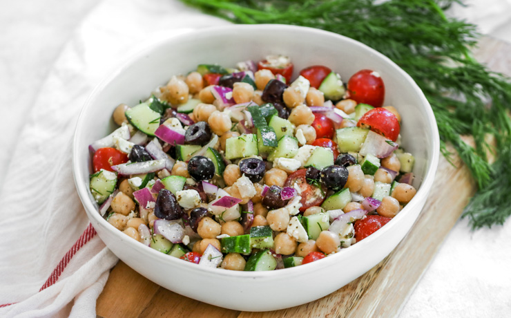 a close up shot of Mediterranean Chickpea Salad in a white bowl