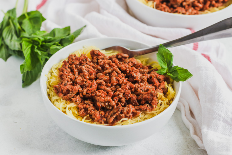 a close up image of a white bowl with Spaghetti Squash and Ground Turkey with a bunch of basil to the side