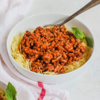 a white bowl with Spaghetti Squash and Ground Turkey and a white napkin with a red stripe
