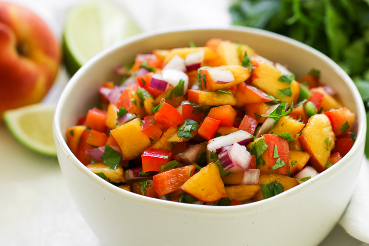chopped peached, red onion, peppers, and cilantro in a bowl
