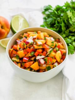a close up of peach salsa in a bowl with a peach, lime, and cilantro next to it