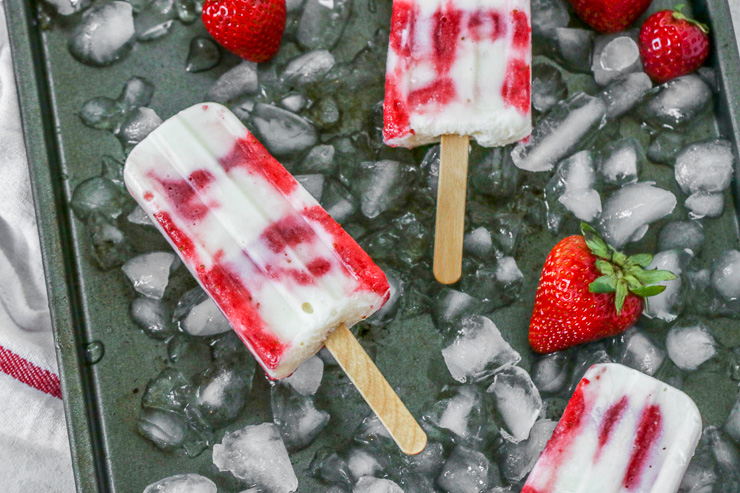 three strawberry yogurt popsicles on ice with strawberries