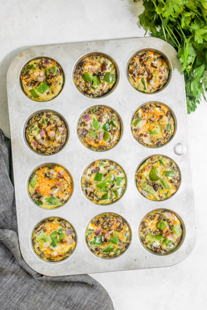 a tray of 12 veggie egg muffins in a muffin tin