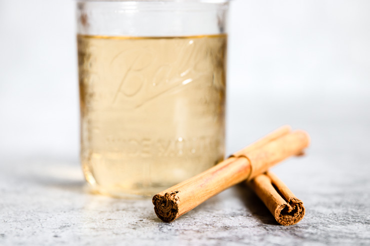 an up close image of cinnamon sticks with the mason jar behind it