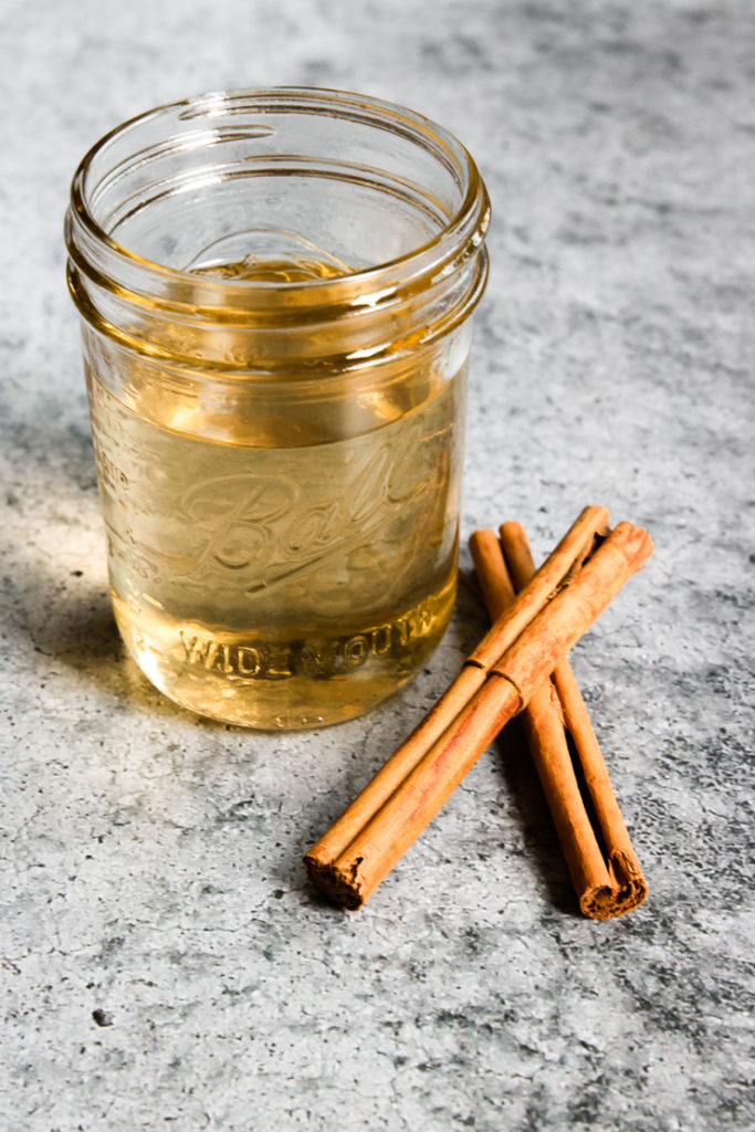 a mason jar of light brown syrup with cinnamon sticks next to it