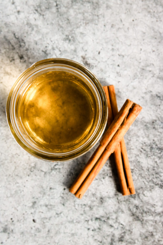 an overhead shot of simple syrup and cinnamon sticks