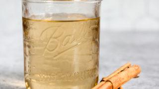 a mason jar of cinnamon simple syrup and cinnamon sticks