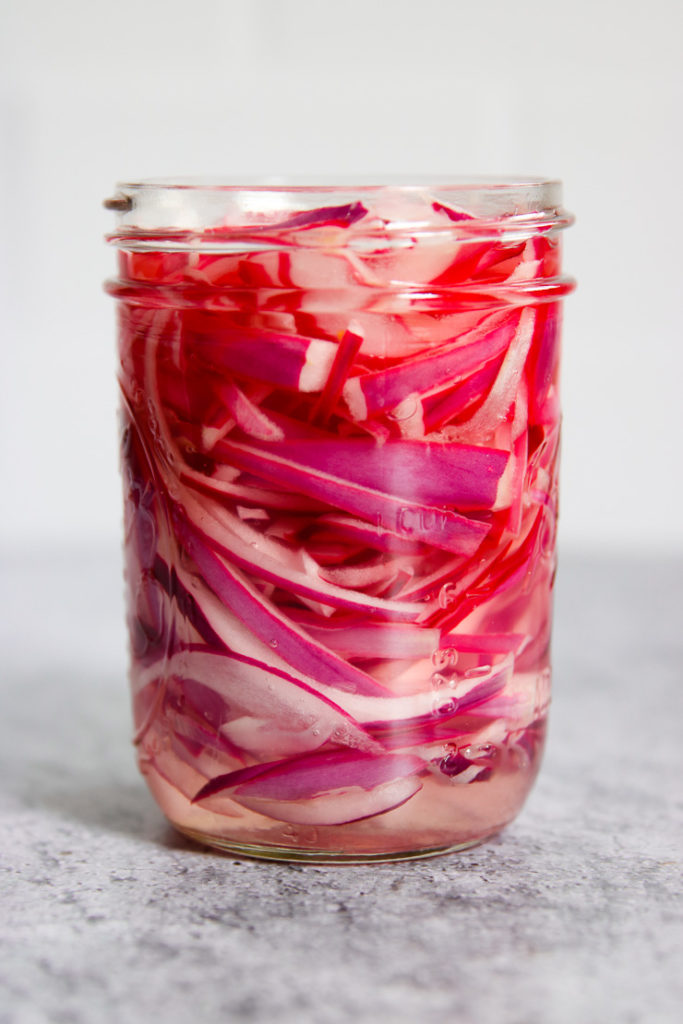a mason jar of red onions with vinegar added