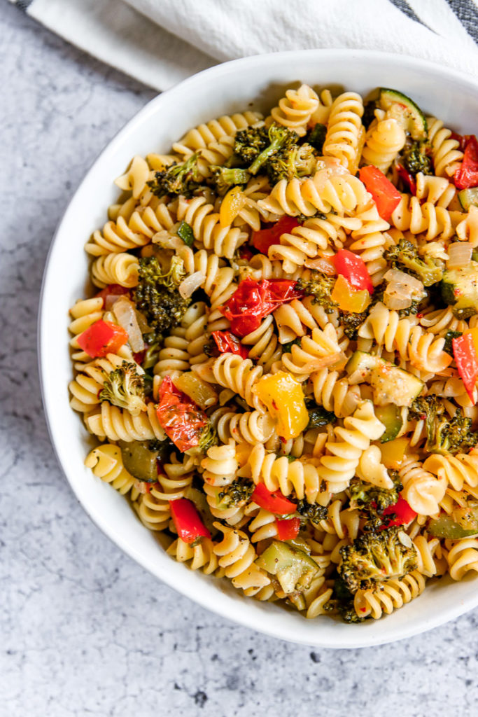 a close up of roasted vegetable pasta in a large white bowl