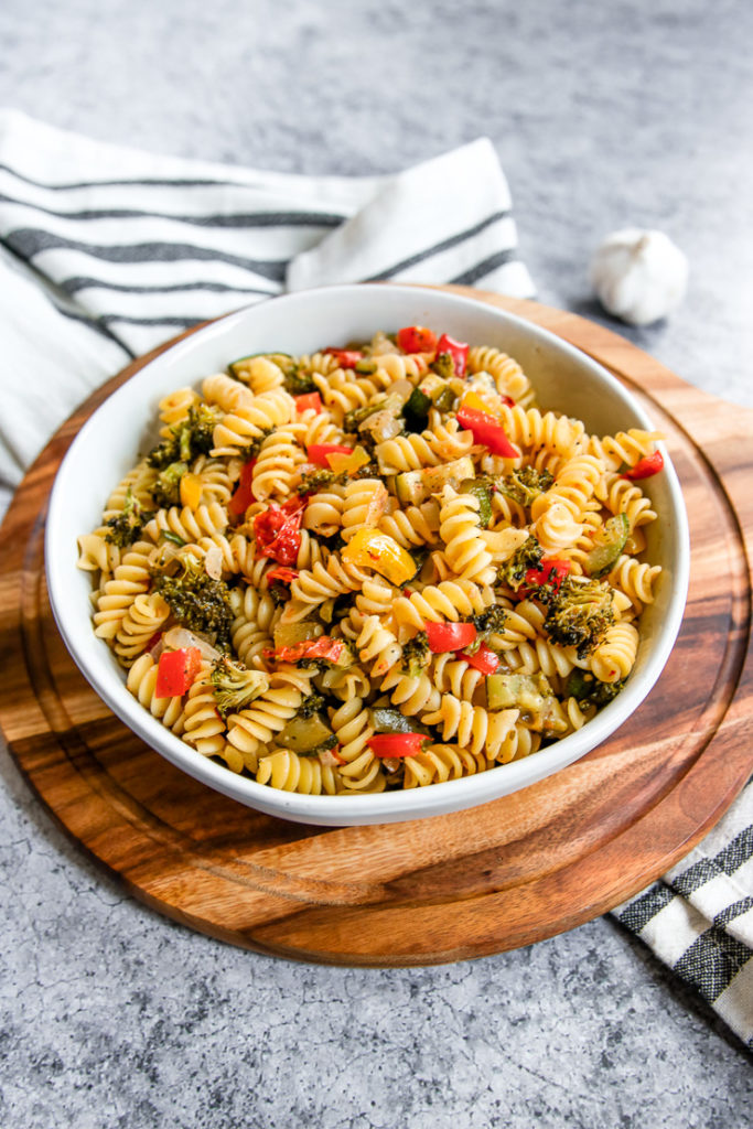 a white bowl full of roasted vegetable pasta