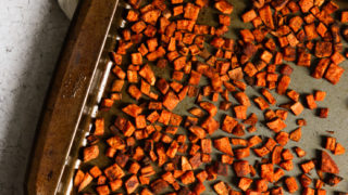An overhead shot of chopped crispy roasted sweet potatoes on a baking dish