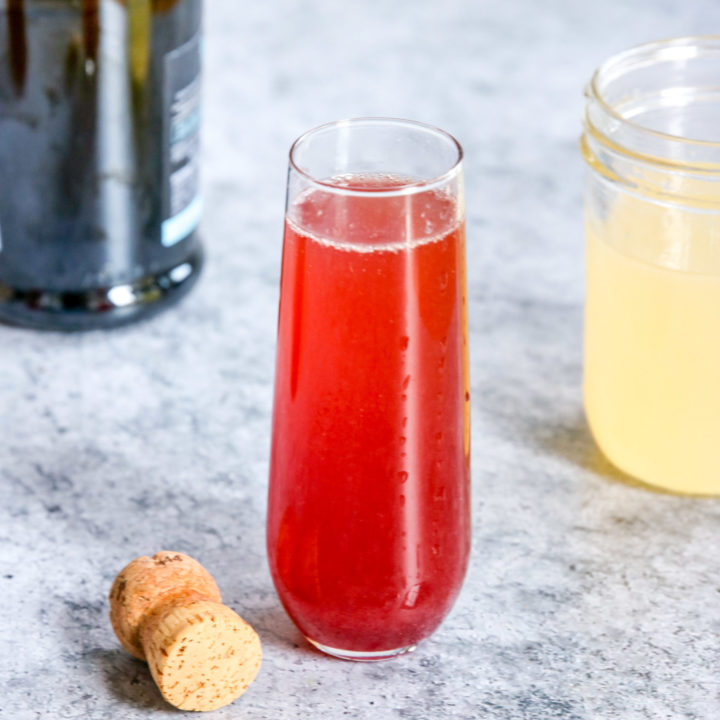 A glass of Pomegranate Mimosa next to a champagne bottle, cork and mason jar of Sour Mix