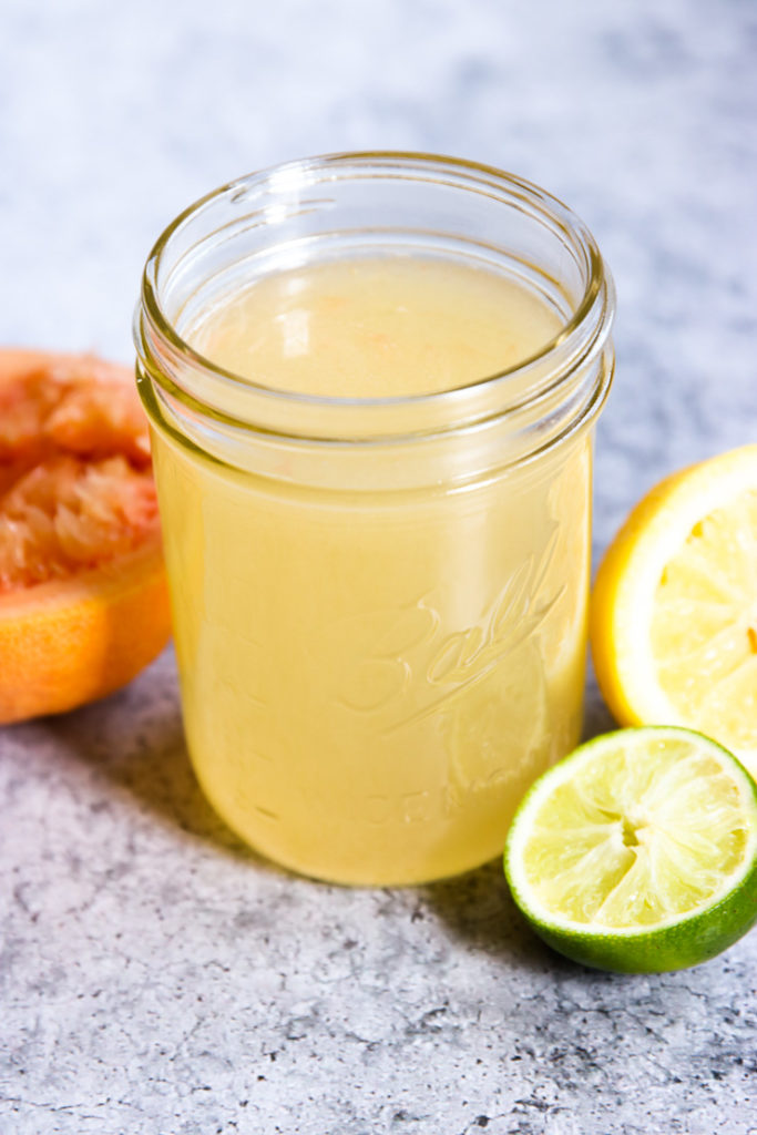 A mason jar full of Homemade Sour Mix surrounded by squeezed citrus fruit