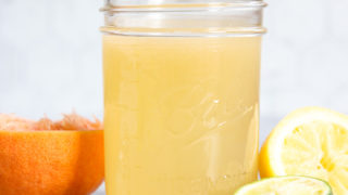 A side view of a mason jar filled with Homemade Sour Mix and squeezed citrus fruit