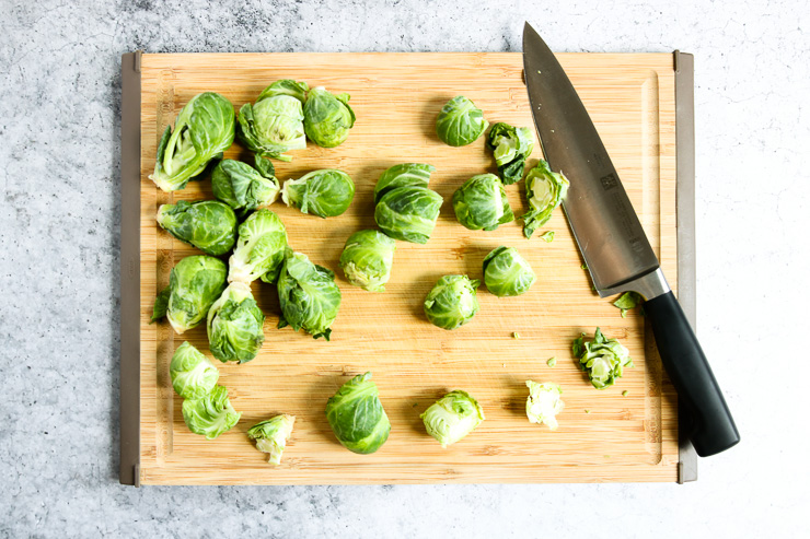 cutting board showing the ends of the brussels sprouts cut off