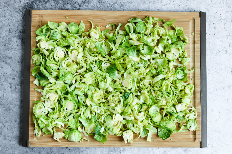 thinly sliced brussels sprouts spread out on a cutting board