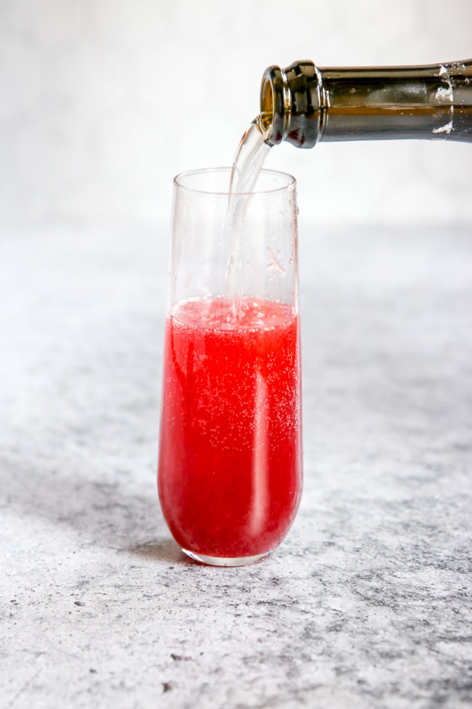 A side view of a bottle pouring champagne into a glass filled with Pomegranate Mimosa