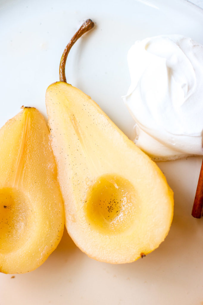 a close up of a halved pear with vanilla bean seeds and whipped cream
