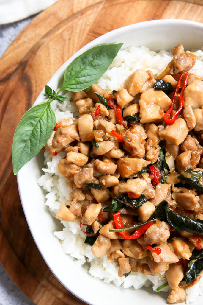 a close up shot of thai basil chicken with thai basil and sliced red chilies
