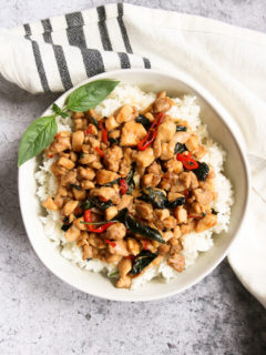 an overhead shot of a bowl of thai basil chicken over rice with a sprig of thai basil