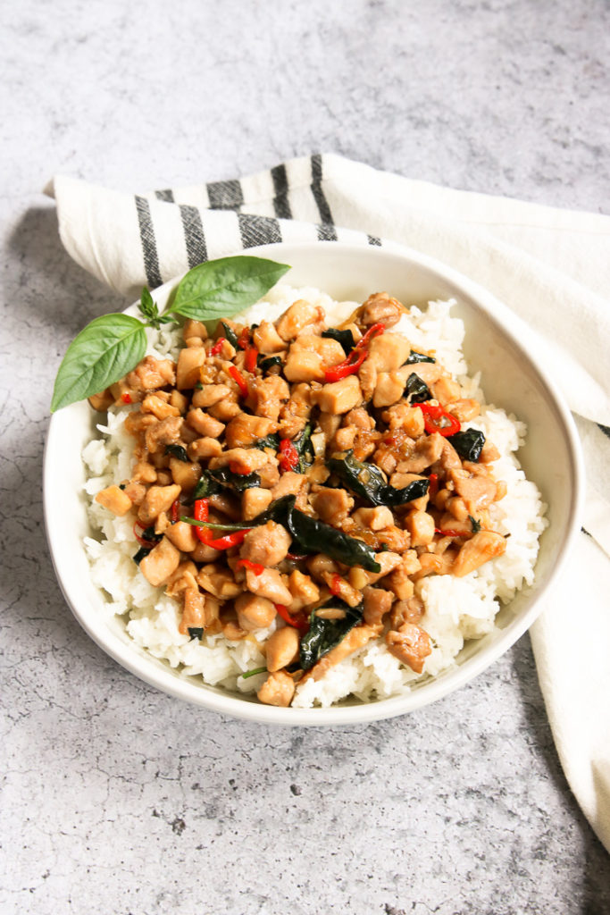 a bowl of thai basil chicken over rice with a sprig of thai basil