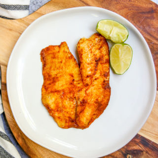 an overhead shot of chili lime tilapia on a white plate on a serving platter