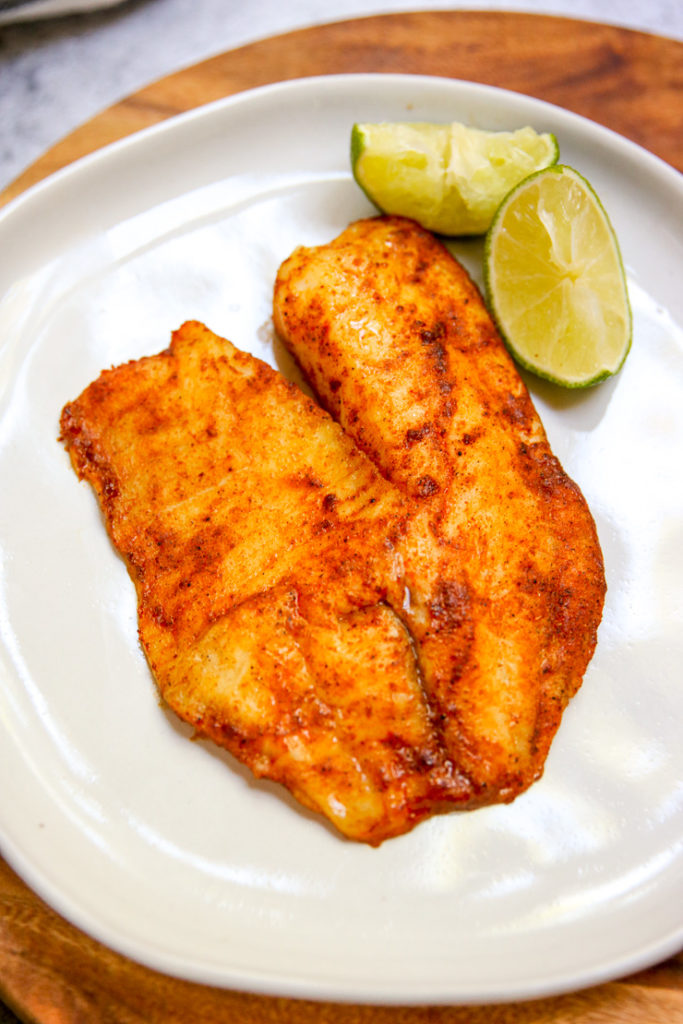 a close up of a seasoned filet of tilapia with a lime
