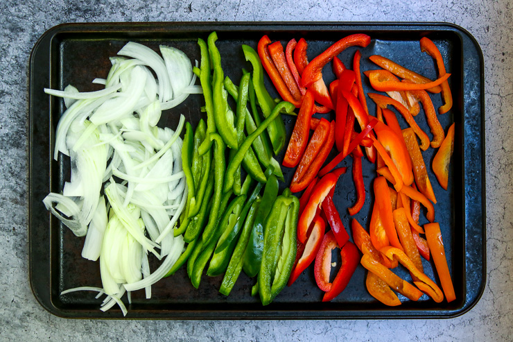 a cookie sheet full of raw, sliced onion, green bell peppers, red bell peppers, and orange bell peppers