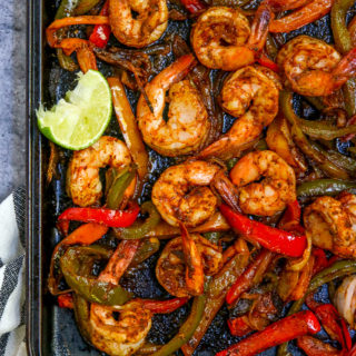 a close up of the cooked shrimp, peppers and onions on a cookie sheet