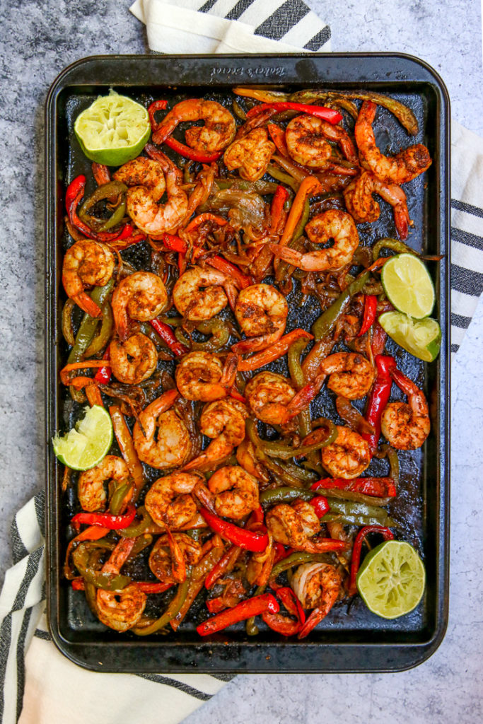 a cookie sheet full of cooked shrimp, onions, and peppers with lime wedges
