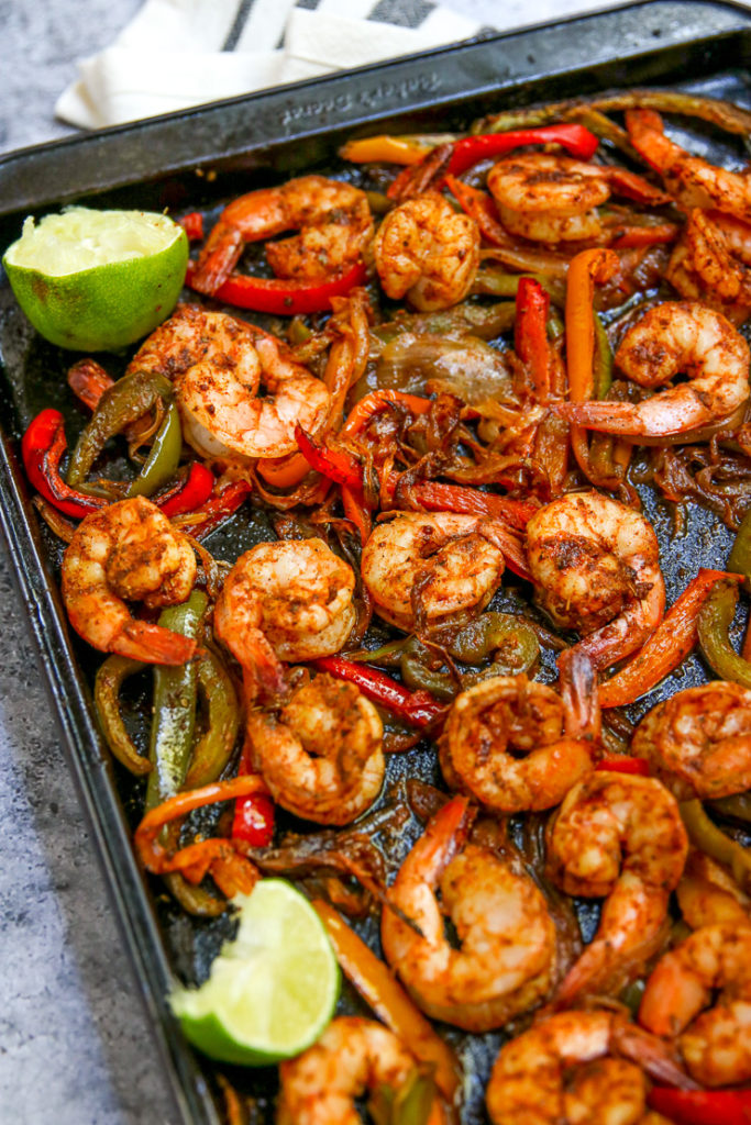 a close up of seasoned cooked shrimp, onions and peppers with lime wedges