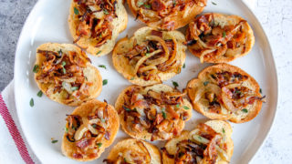 a plate of bacon caramelized onion crostini