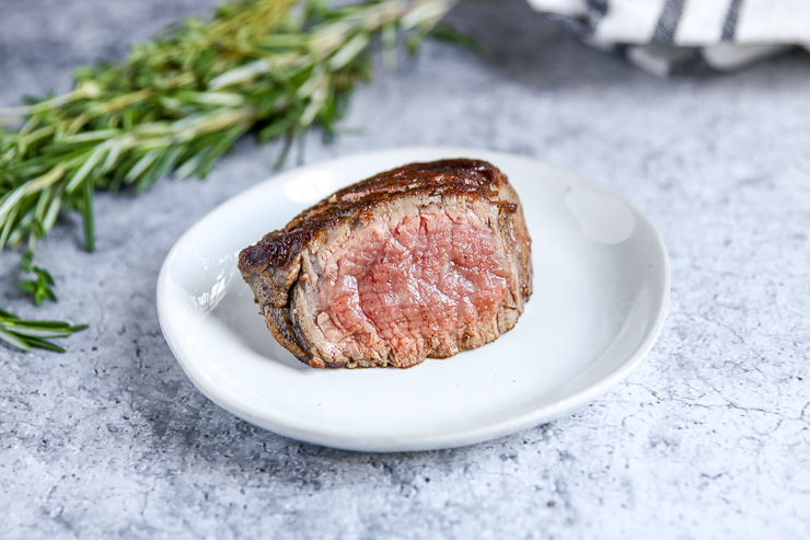 a sliced piece of filet mignon showing a light pink center