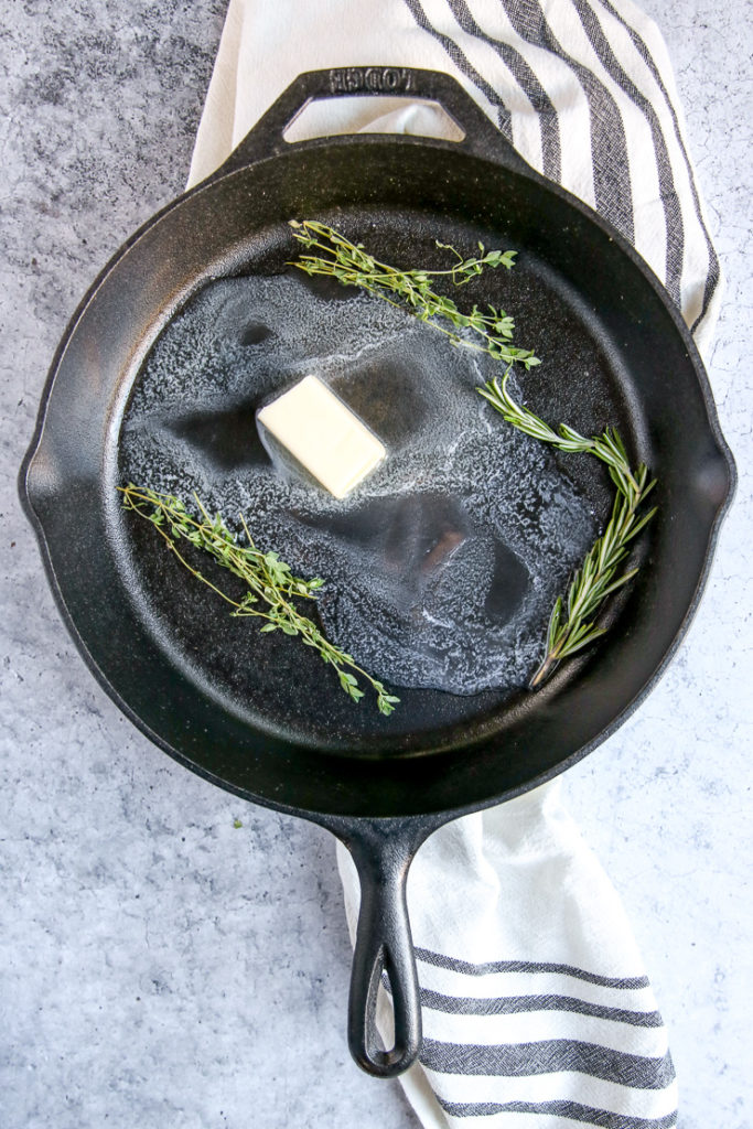 a cast iron skillet with partially melted butter, thyme, and rosemary