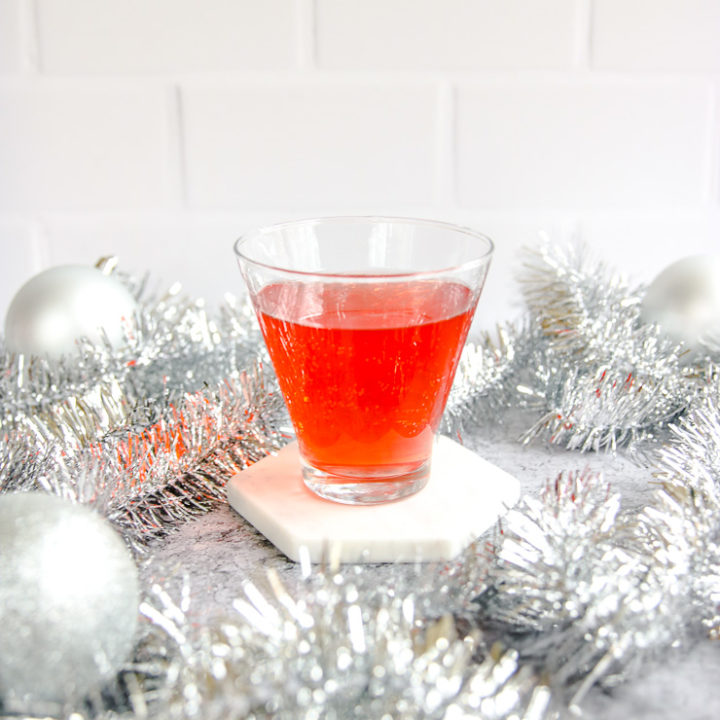 a stemless martini glass with cranberry ginger ale punch surrounded by silver garland and baubles