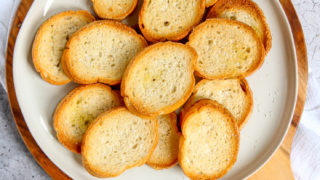 an overhead shot of toasted crostini with olive oil, garlic, and salt