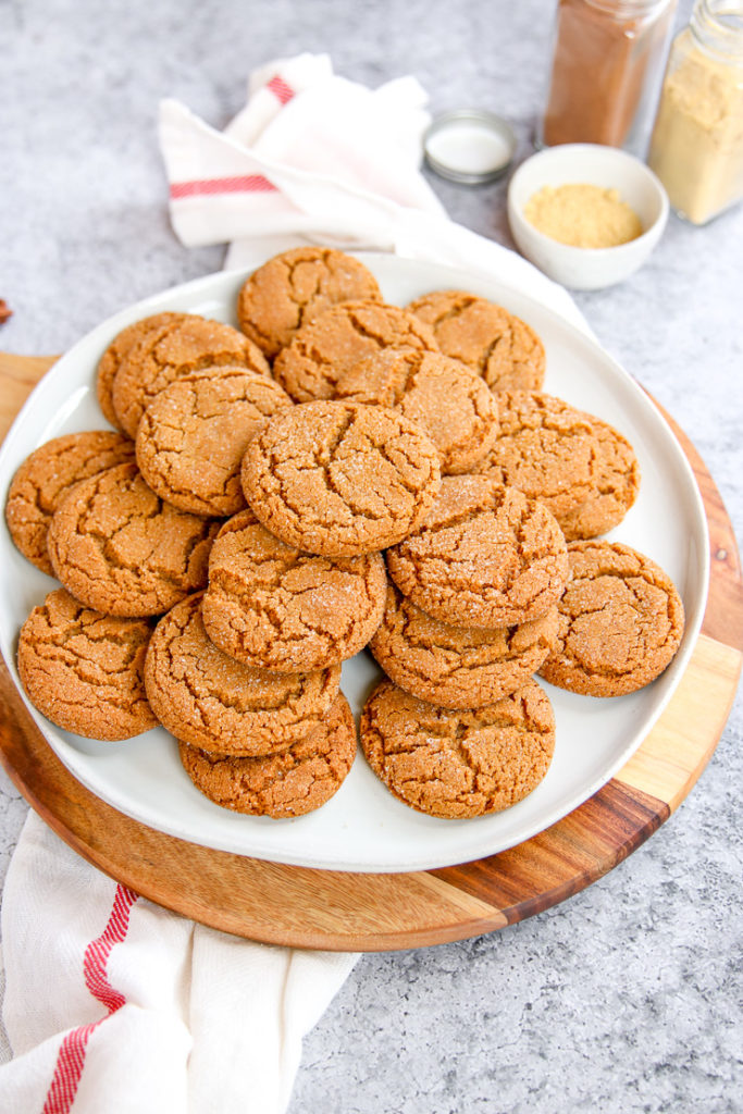 a pile of ginger snaps with jars of spices in the background