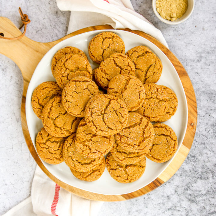 a white plate of ginger snaps on a wood platter next to a napkin
