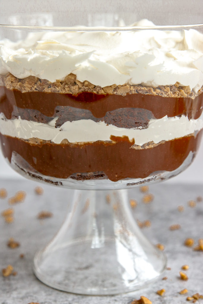 layers of brownie, pudding, heath crumbles and cool whip in a glass serving container