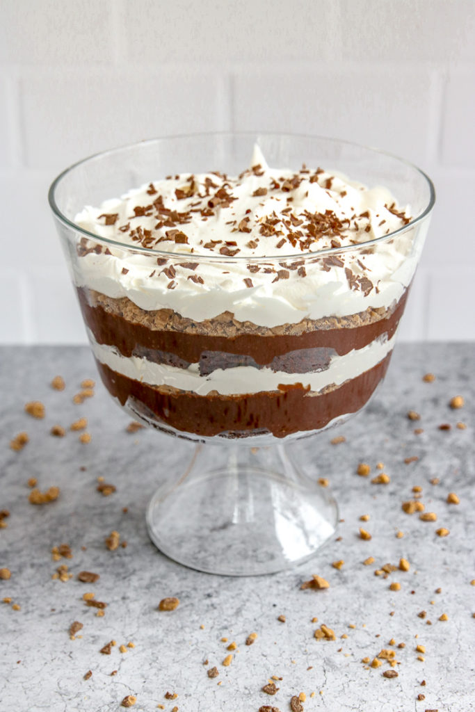 a heath bar trifle in front of subway tile on a gray table with heath bars crumbled