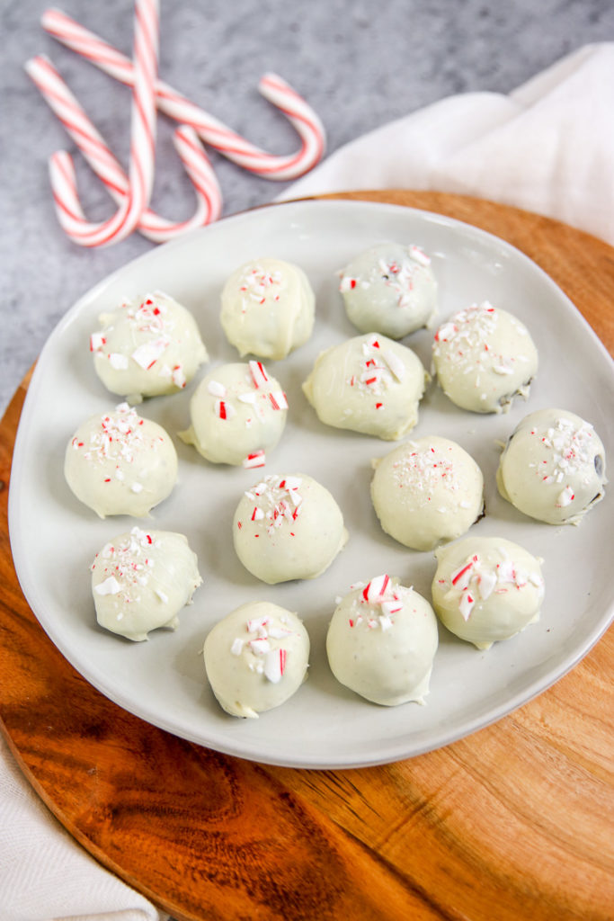 a plate of peppermint oreo truffles on a wooden platter
