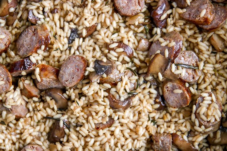 a close up of sliced sausage, mushrooms, and arborio rice