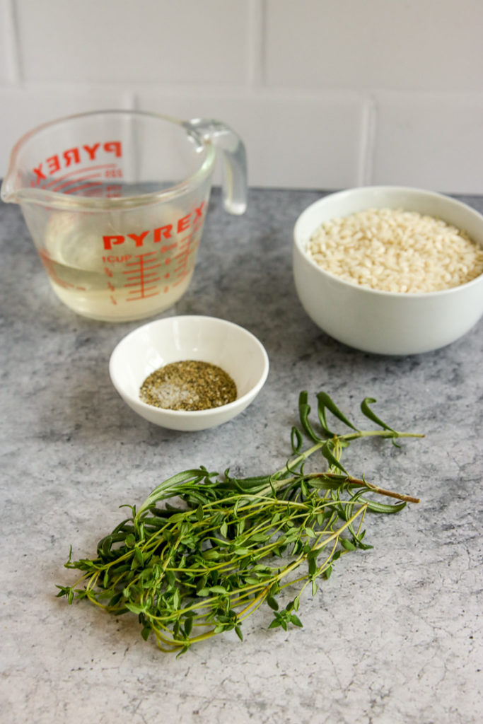 fresh thyme and rosemary, a bowl of salt and pepper, arborio rice, and a glass measuring cup full of white wine